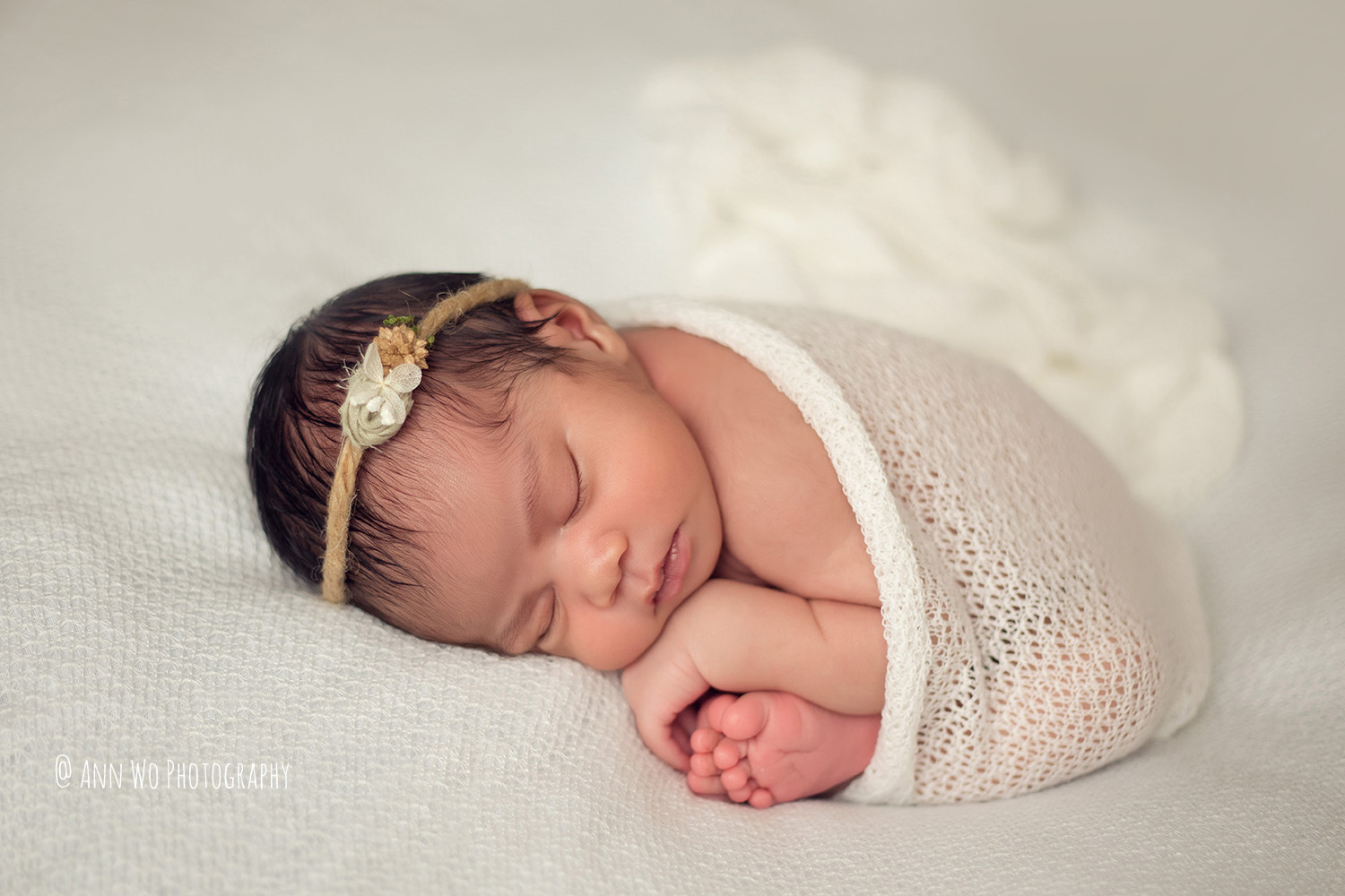 newborn baby in cream cozy set up - Ann Wo Photography London