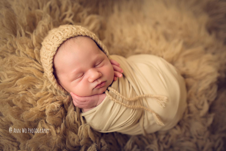 wrapped newborn baby on honey flokati