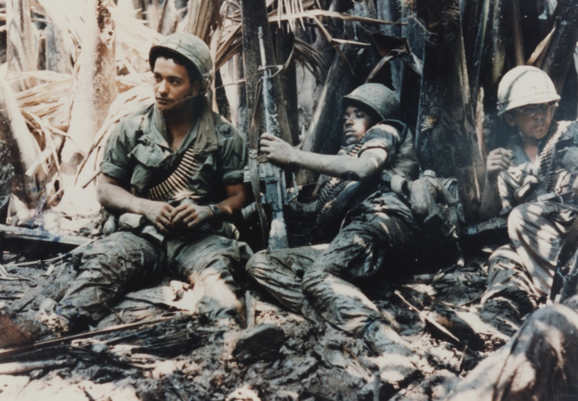 Privates First Class Carl Baden (New Orleans, Louisiana) and Arcadio Carrion (Puerto Rico) of Company B, 3rd Battalion, 47th Infantry, 9th Infantry Division, laying in the mud waiting for artillery to knock out the 50 Cal. Machine gun bunker that has them pinned down in a tree line at My Tho.