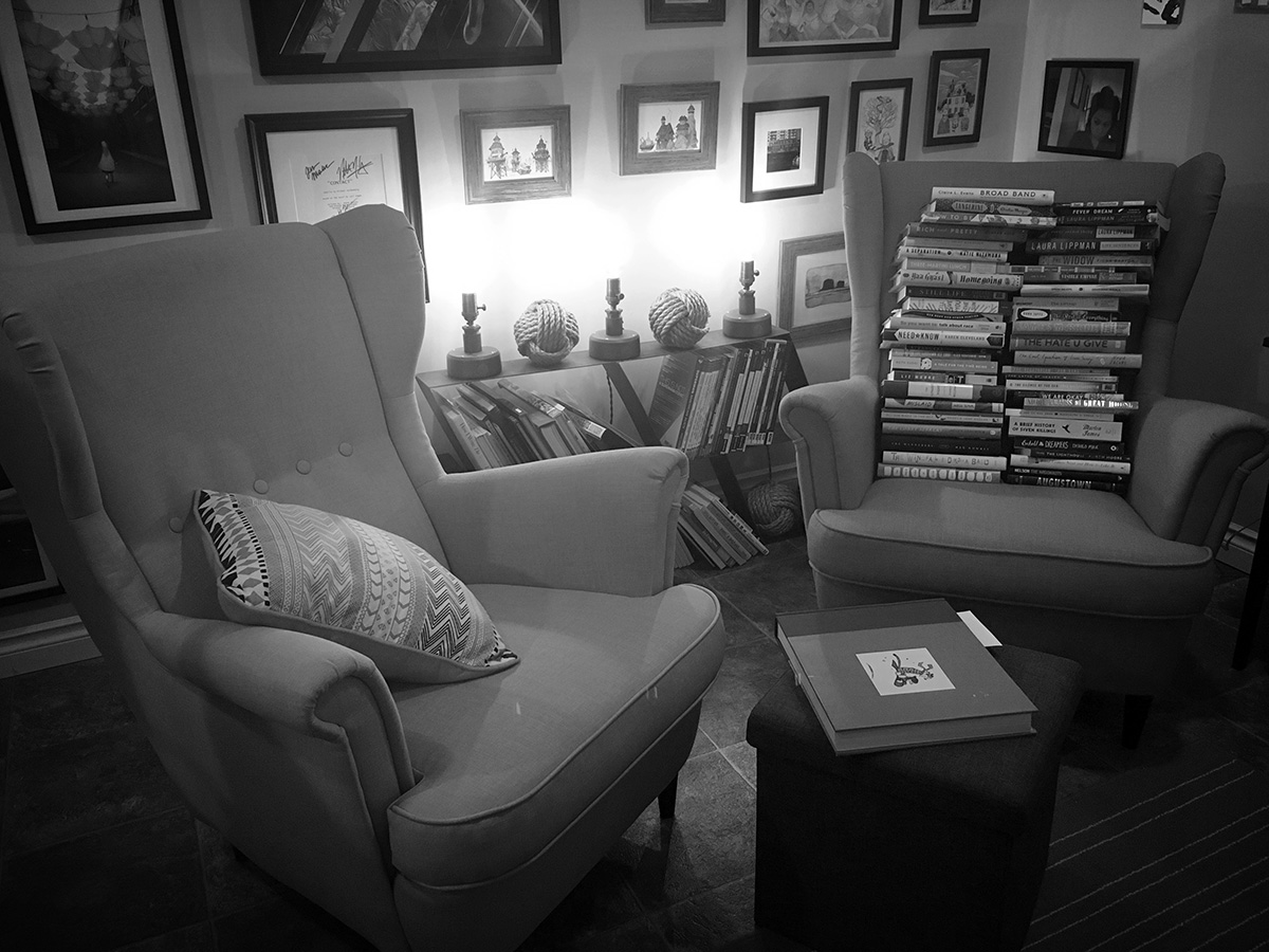 Squish's chair, at left, with a copy of  Calvin & Hobbes on the ottoman; my overly ambitious 2018 to-be-read stack at right.