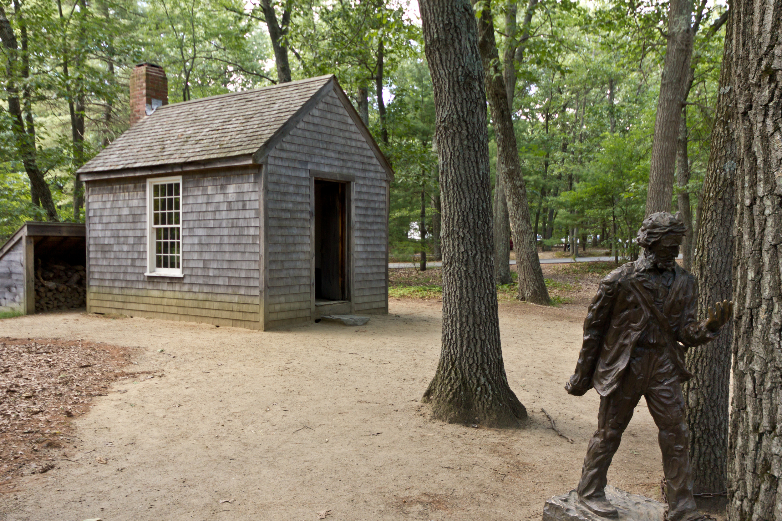 Replica_of_Thoreau's_cabin_near_Walden_Pond_and_his_statue.jpg