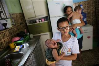 Paulo, 8, holds his five-month-old sister Laura as his grandmother Manyara (back), 46, holds her five-month-old grandson Lucas at their house in Santos, Sao Paulo state, Brazil on April 20, 2016. Jaqueline Jessica Silva de Oliveira hoped doctors were wrong when a routine ultrasound showed that one of her unborn twins would be born with the condition, marked by stunted head size and developmental issues.    NACHO DOCE / Reuters