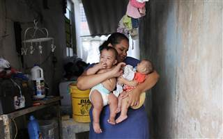 Jaqueline, 25, holds her five-month-old twins, Laura (R) and Lucas at their house in Santos, Sao Paulo state, Brazil. Laura was born with microcephaly while her twin brother Lucas does not suffer from the condition.    NACHO DOCE / Reuters
