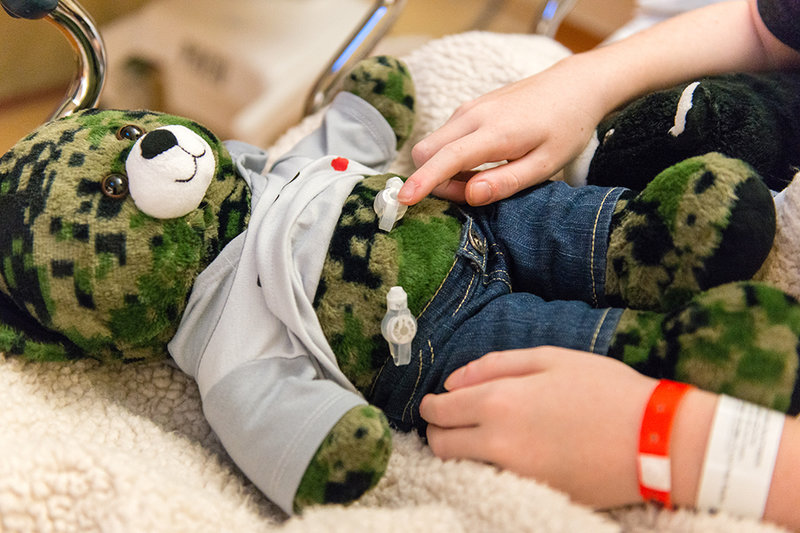 Matthew Husby points to a gastrostomy tube on his teddy bear that is similar to the one surgeons inserted in his own stomach. Role-playing helps kids relax, doctors say.   Heidi de Marco/Kaiser Health News