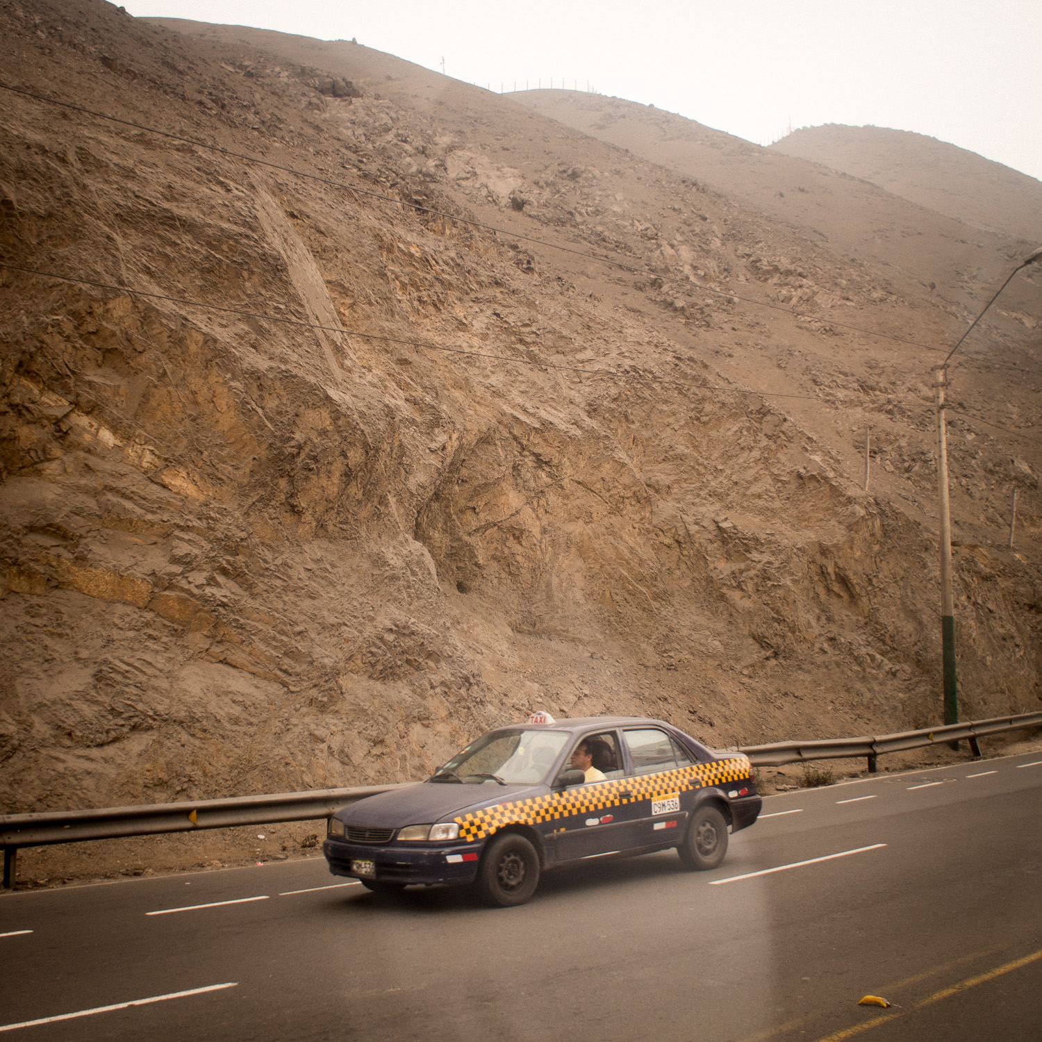 A taxi in front of one the barren hills nestled around Lima. COY was hosted at an agricultural university just beyond this hill. Photo: Benjamin Brooking
