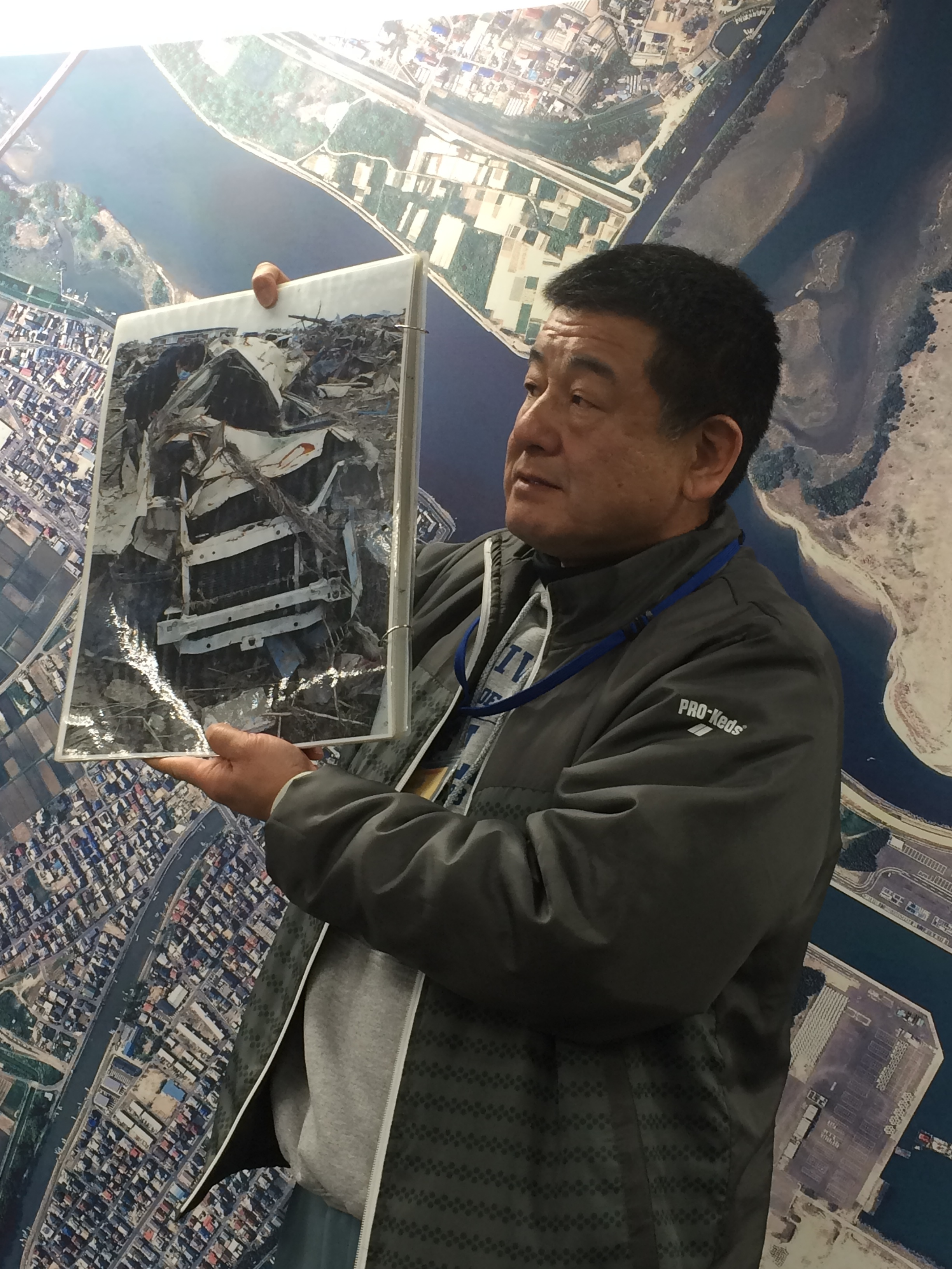 Figure 3:Nakamuna showing a picture of his truck crushed by debris.