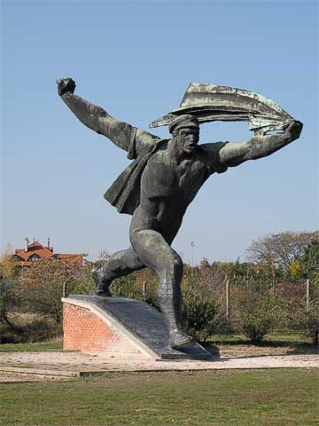 """""""Republic of Councils Monument"""" represents a communist worker holding the Soviet flag, charging into the future. When the statue was originally installed, apparently Budapest residents thought it looked like a thermal bath worker chasing after a customer who had forgotten his towel."""