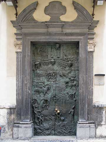 Near the market is the Cathedral of St. Nicholas (Stolna cerkev sv. Nikolaja). This door was created for Pope John Paul II's visit to Ljubljana in 1996. It traces the history of the Slovenes from the original Roman settlement (at the bottom) through the World Wars (represented at the upper left) by the Slovenes going into a cave. At the top is Pope John Paul II.