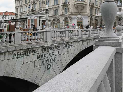 The most memorable bridge of Ljubljana is the Triple Bridge (Tromostovje). The main, central bridge (the one with the writing) was built in 1842, but to help ease the traffic going across, Plečnik added two side bridges to match. Instead of making them parallel and identical, the side bridges are narrower (for pedestrians only) and the bridges form a fan.