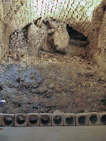 Excavation is still being done in several parts of the cellars, including this, the southwest corner. Before excavation started, the cellar was filled with waste and sewage. The blocks in front were sections of Roman pipe.