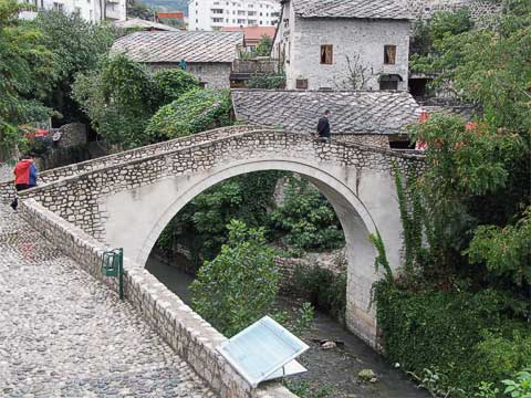 On either side of Old Bridge are the cobbled streets of Old Town. On the west side is the similar but smaller Crooked Bridge (Kriva ćuprija). It predates Old Bridge by about a decade, and was built as a practice run. It was damaged during the war, and was reconstructed after it got swept away by floods several years later.