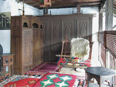 This living room is open to the east, since the wind rarely comes from that direction. The loom would have woven the carpets on the floor, and the chests were used to bring the dowry when a new wife came into the house. The lattice to the right allowed the women to discreetly see what was happening in the courtyard below.