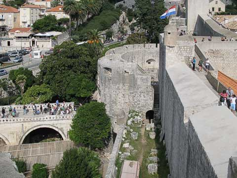 Tourists walking along the west wall, and others going through the Pile Gate. The trees are growing in what was used as the moat.