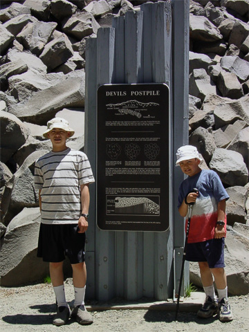 Kellen and Tynor standing by the sign which describes how the columns formed. The basalt cooled and formed cracks straight up and down at 120° angles, creating hexagonal columns.