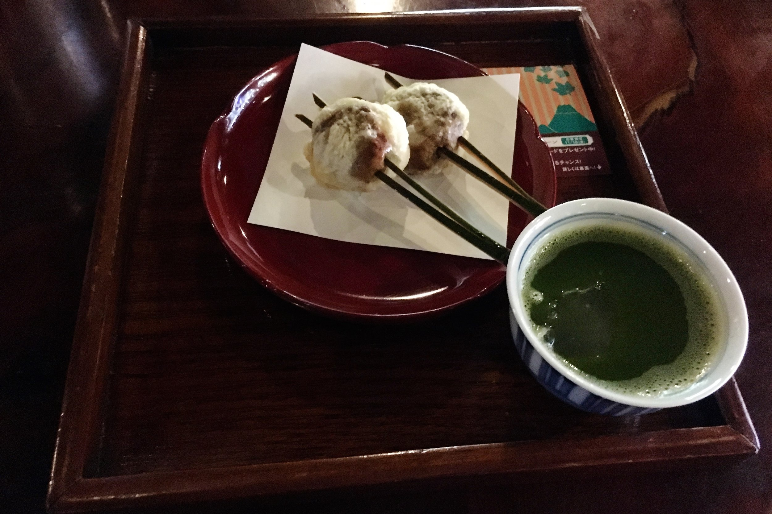 Fried mochi and thick green tea with an ice cube in it