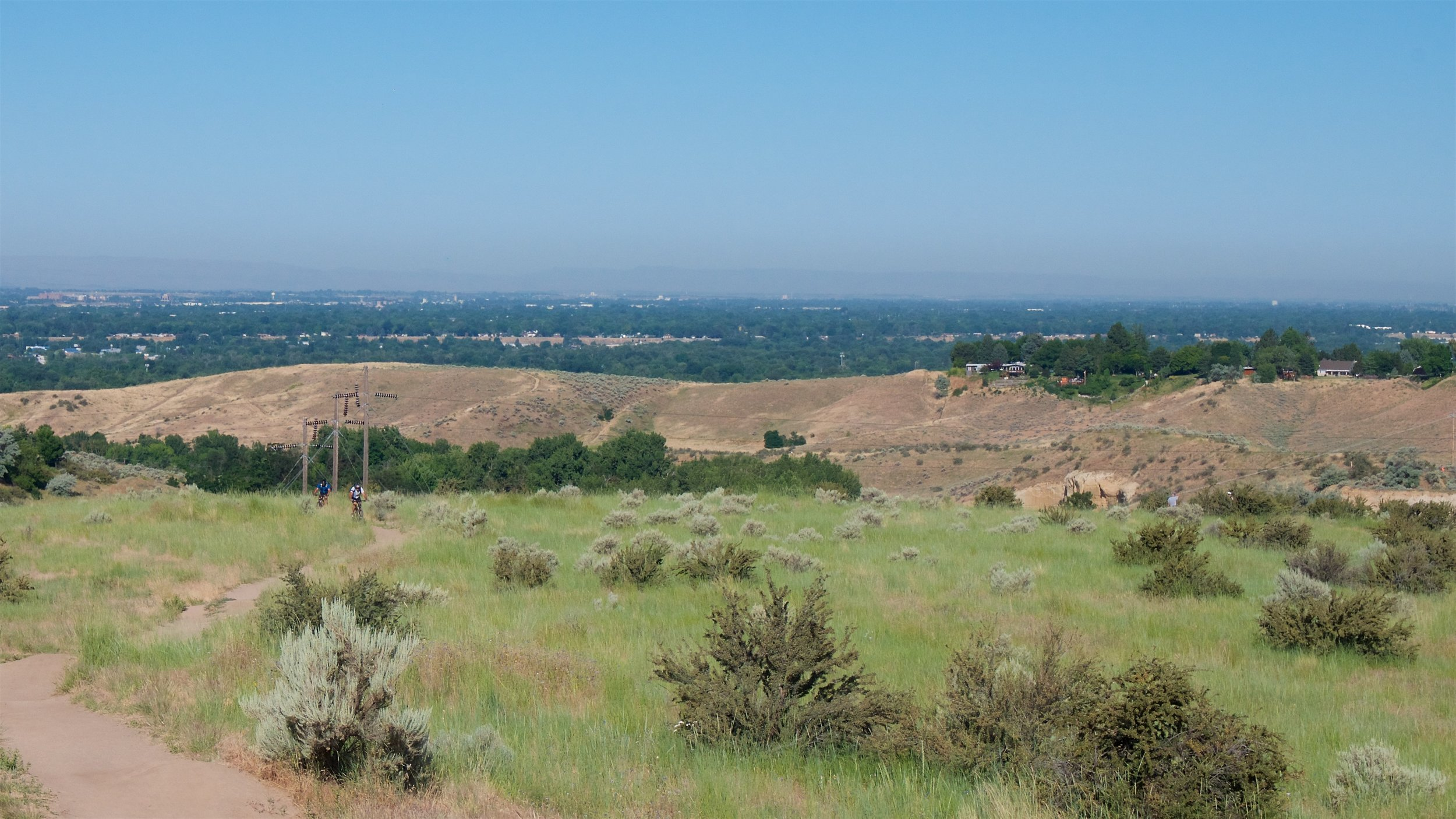 Mountain bikers on the trail; view of the city