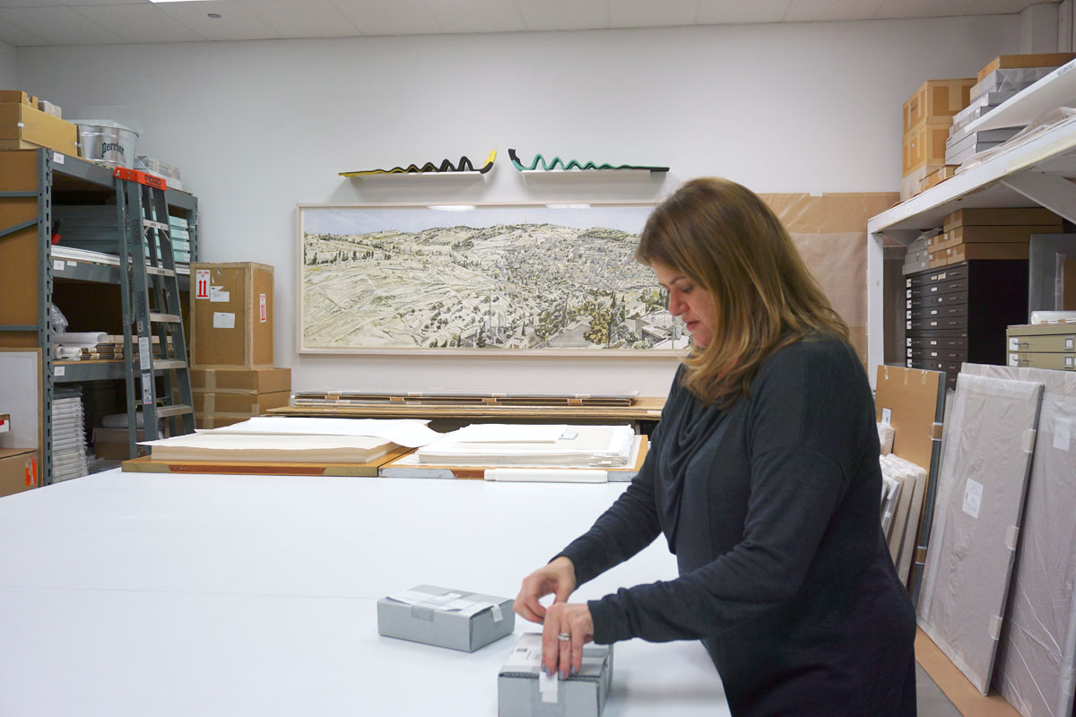 "© 2019 Louise Levergneux.  On wall in background:  Philip Pearlstein,   Jerusalem, Kidron Valley  , 1989, heliorelief with roulette on wood, 40 x 119"". Kristin opening the boxes that contain Ed Ruscha's artists' books  Me and The , and  OH NO."