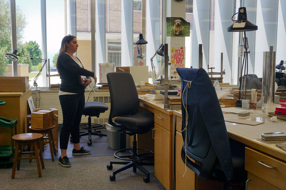 © 2019 Louise Levergneux. Victoria Birth, Binding Supervisor in front of her desk at the Harold B. Lee Library's Book Repair Unit.