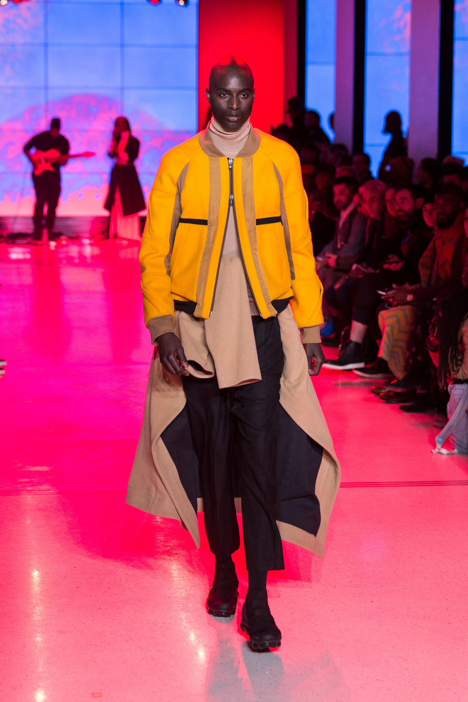 LOOK 29   ARC Flight Jacket  / Rover Yellow   ARC Orison Coat  (Worn On Waist) / Camel   ARC Turtleneck  / Camel   ARC Ankara Pant  / Black Wool   Nike Air VaporMax Utility