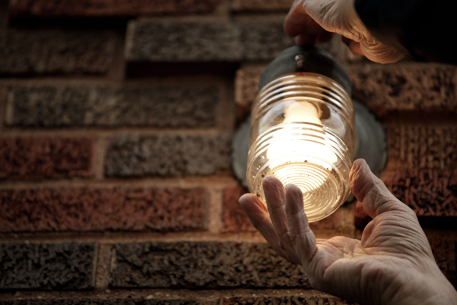 After putting in a new light bulb, Nick DiNunzio replaces the protective cover for the light on a home in his neighborhood on Monday, Oct. 28, 2013 in Detroit.  Tim Galloway / Special to DFP