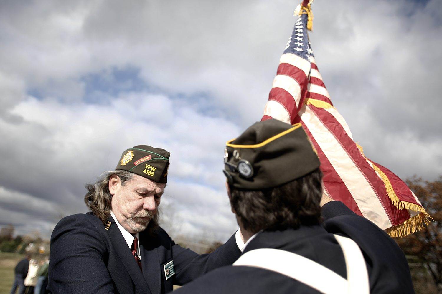 Scott Gloger, left, from Brighton and Darrell Poole from Wixom unfurl the flag to prepare for the Veterans' Day ceremony on Sunday, Nov. 10, 2013 at the White Lake Cemetery in White Lake.