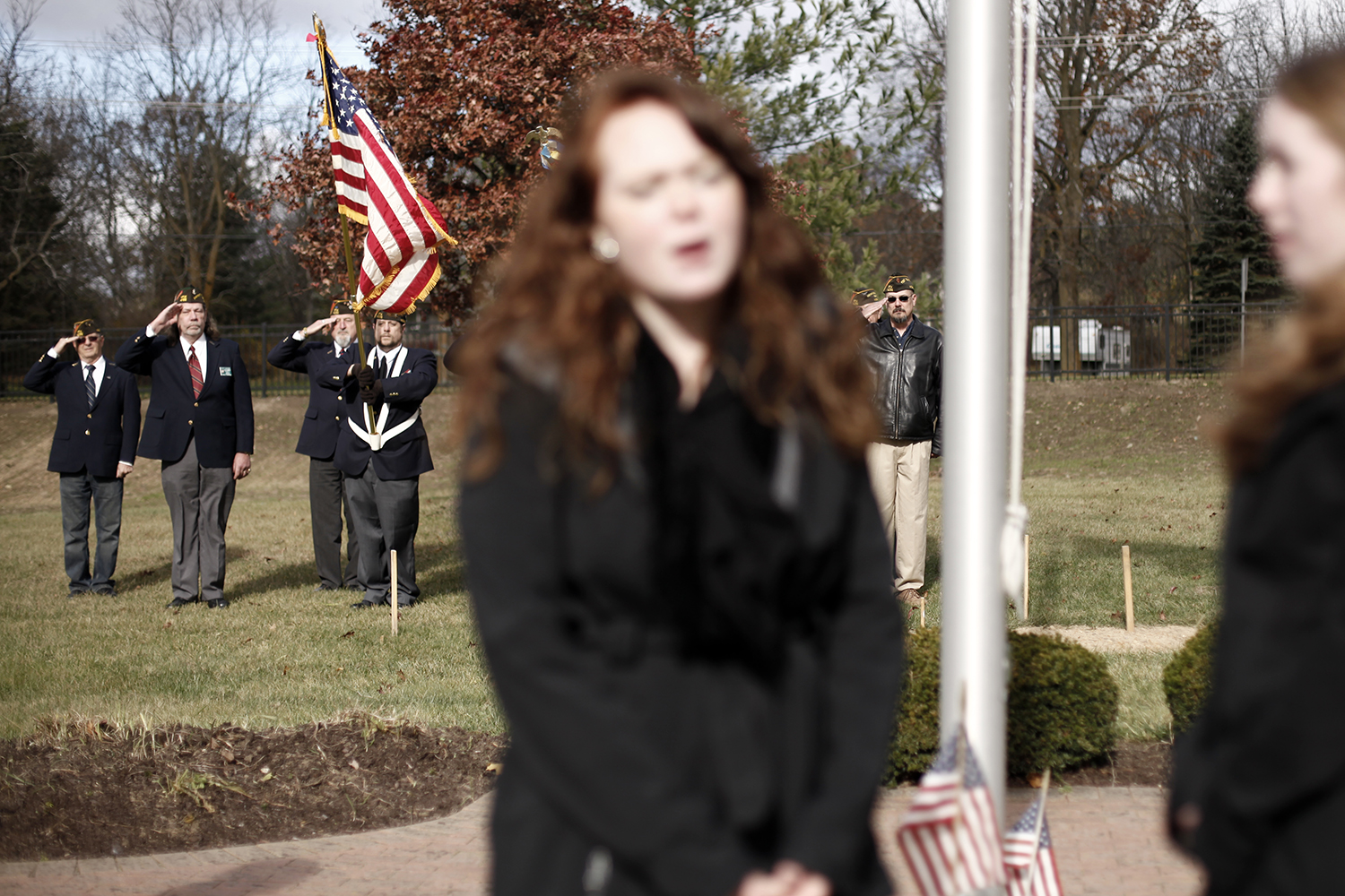 Veterans and members of the color guard salute while Erika Johnson, center left, and Anna George, right, both from Commerce Township, sing the National Anthem on Sunday, Nov. 10, 2013 at the White Lake Cemetery in White Lake.