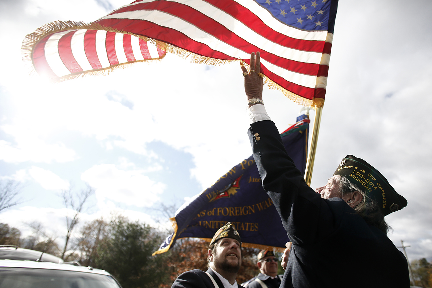 Scott Gloger from Brighton, right, tries to grab the flag while Darrell Poole from Wixom looks up on Sunday, Nov. 10, 2013 at the White Lake Cemetery in White Lake.