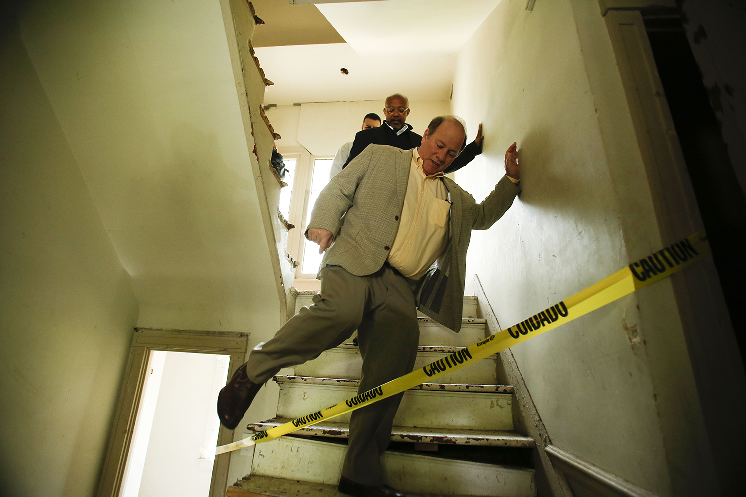 Mayor Mike Duggan steps over caution tape in a home on the Boston Edison Auction Tour on Sat., May 17, 2014 in Detroit. Many of the homes had areas restricted by caution tape and the tour required the signing of a waiver due to potentially dangerous areas in the houses. Tim Galloway/Special to DFP