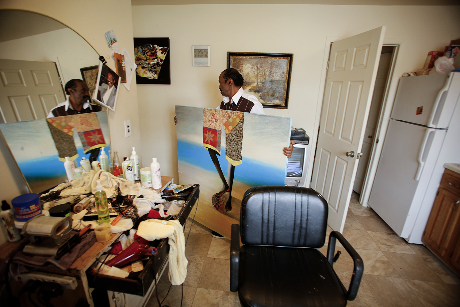 Michael Horner, 66, carries a piece of his art through his styling area on Saturday, May 3, 2014 in his home in Detroit. Tim Galloway for Al Jazeera America