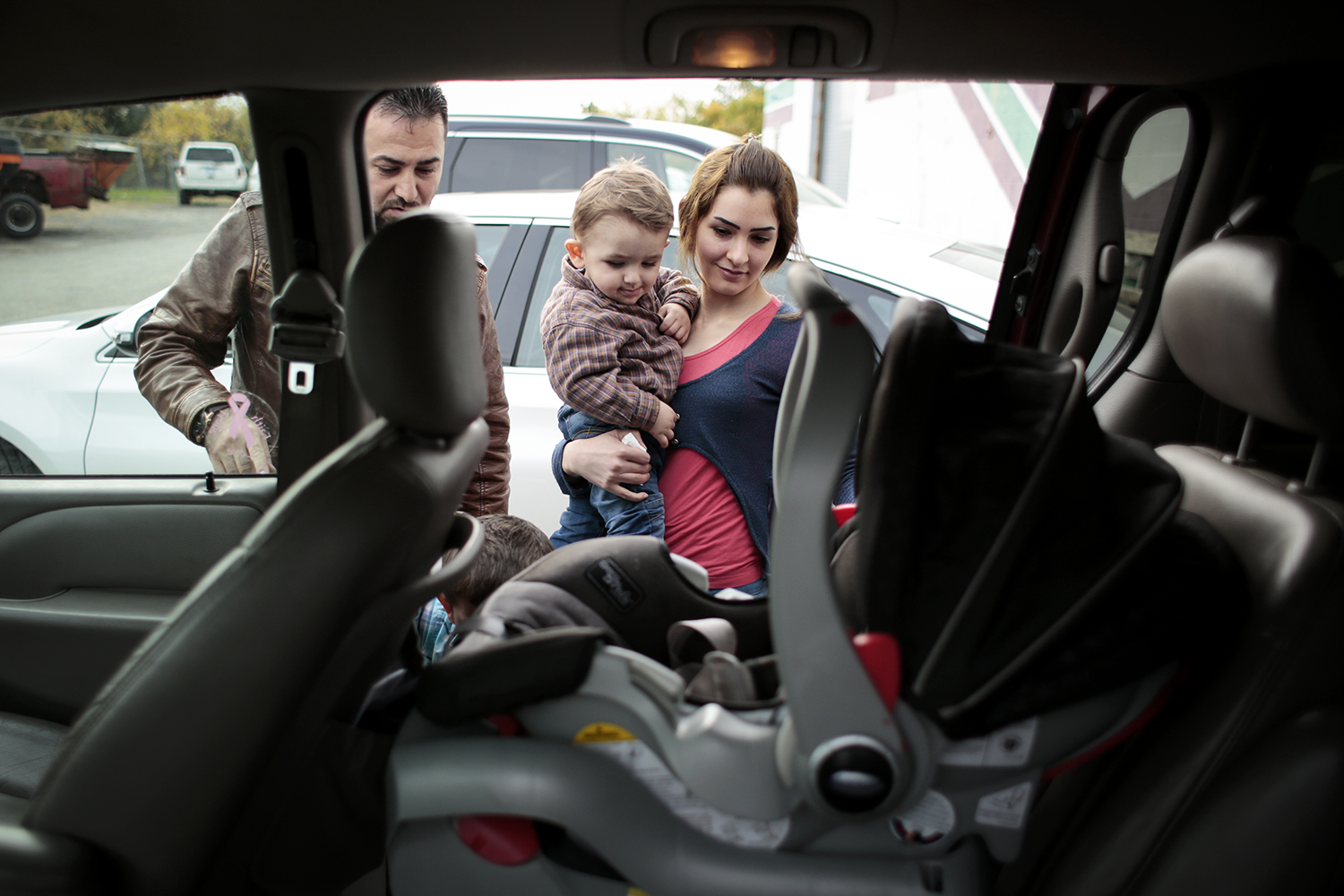 Waseem Ilotte, left, and his wife Lara Al Aso, right, load their son Aras Ilotte, 18 months old, all from Warren, into their vehicle after receiving aid at the Chaldean American Ladies of Charity Center on Friday, Oct. 10, 2014 in Troy. Tim Galloway/Special for DFP