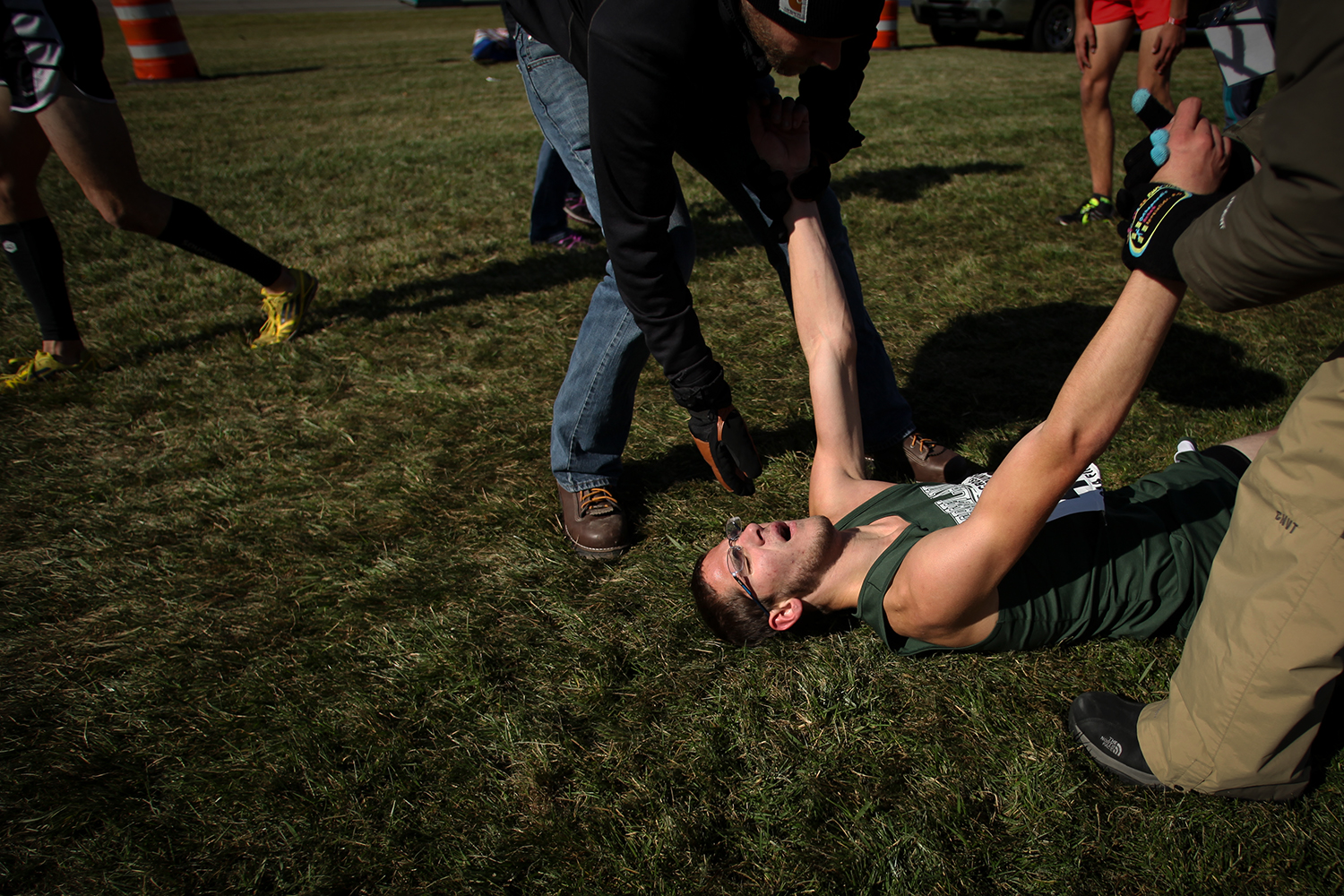 Freeland's Alex Stowell (Senior) is helped off the ground after completing the race at the 2014 Lower Peninsula Cross Country Division 2 Championship on Saturday, Nov. 1, 2014 at the Michigan International Speedway in Brooklyn. Tim Galloway/Special to DFP