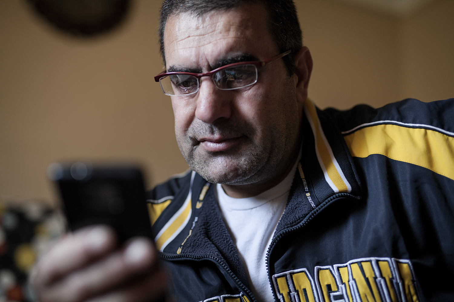 Dearborn, MI - Thursday, Nov. 19, 2015: Mohamad Al Mohsen tears up while looking at old photographs sent to him by family in Jordan in the living room of his home on Thursday, Nov. 19. 2015 in Dearborn, MI. Al Mohsen said that going through the photos is sometimes happy and sometimes makes him cry.