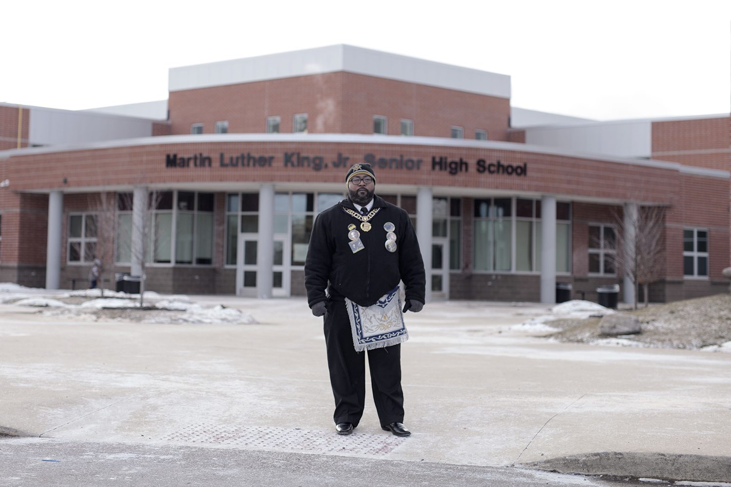 Deangelo Hayes from Detroit, a member of the Masonic Lodge, stands outside in the cold after the 7th Annual Martin Luther King Jr. Legacy March at Martin Luther King Jr. High School on Monday, Jan. 18, 2016 in Detroit. Hayes, having been at the inaugural march, says it's important to continue the tradition of involvement between the Masonig Lodge and the high school, not only with the annual march but with mentorship as well. Tim Galloway/Special for DetNews