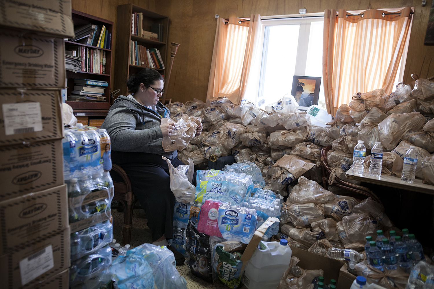 Genesee Twp. resident Samantha Baumgarner stretches a plastic grocery bag to fill with bottled water at the Mission of Hope - Universal Life Church on Wednesday, Jan. 20, 2016 in Flint, MI. Each bag is filled with six bottles of water, the allotted amount for each resident, per day, to be picked up at the mission. Tim Galloway for The Wall Street Journal