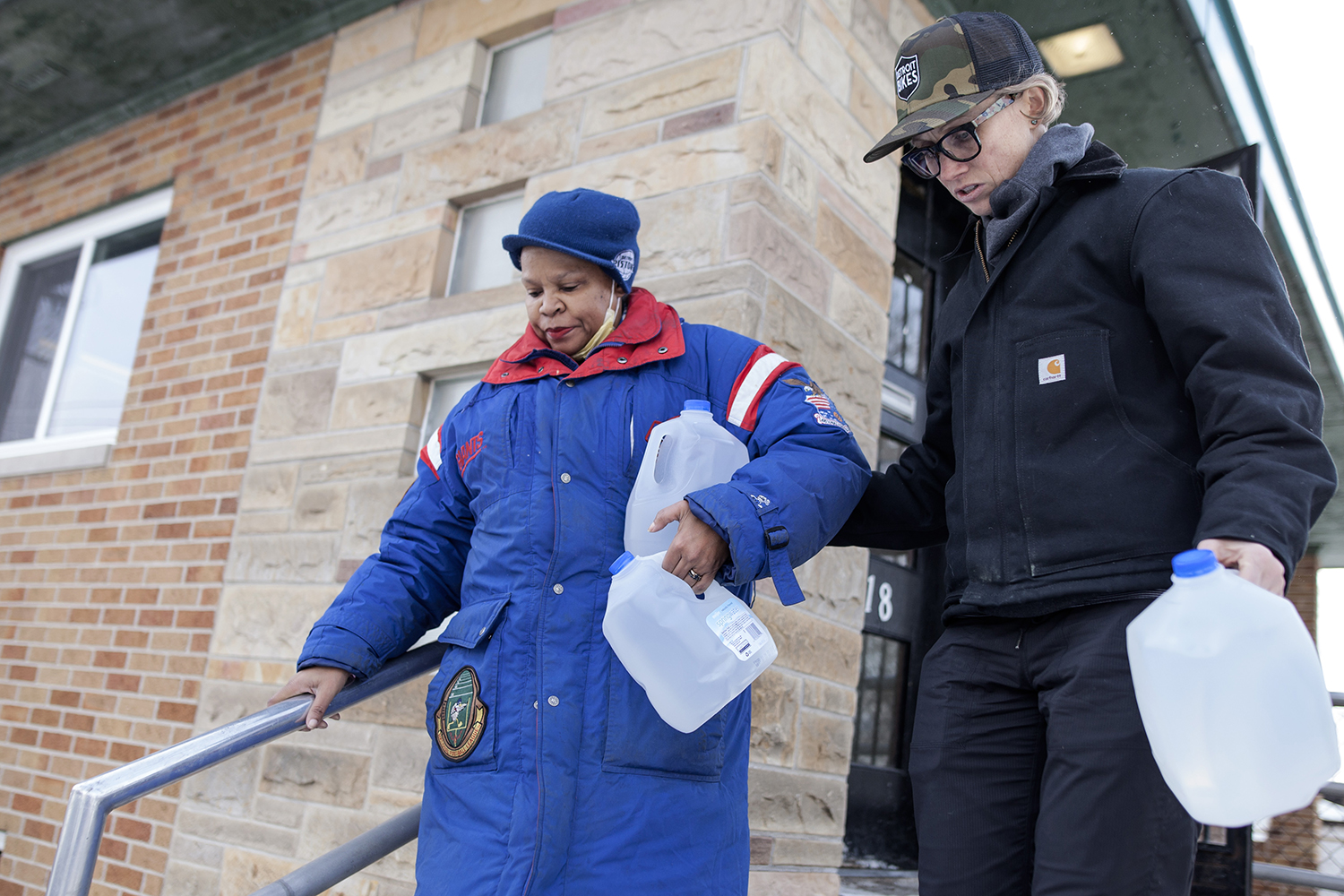 Terra Castro, right, from St. Clair Shores assists Flint resident Christine Brown down a flight of stairs while carrying water to her vehicle at the Mission of Hope - Universal Life Church on Wednesday, Jan. 20, 2016 in Flint, MI. Brown suffered from rashes due to showering under the Flint water. Tim Galloway for The Wall Street Journal