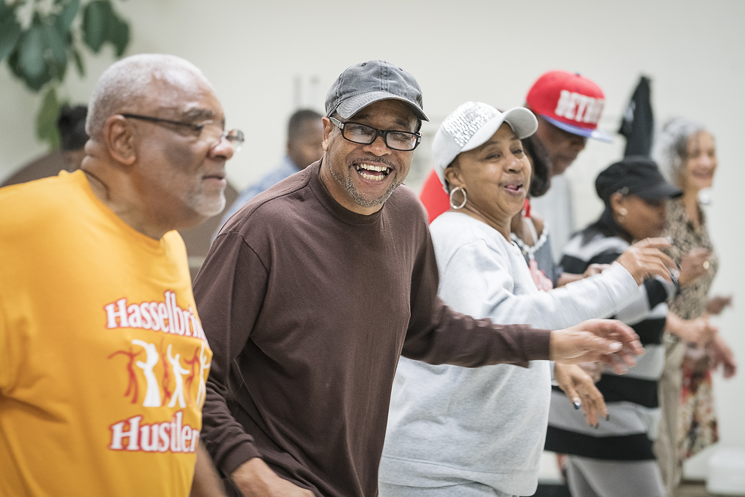 Flint, MI - Tuesday, October 24, 2017: DJ Gardell Haralson, 64, center left, laughs as he dances with the Hasselbring Hustlers at the Hasselbring Senior Community Center. Haralson helped grow the Hustlers from a meager 15 participants to approximately 150 over the past four years, simply by word of mouth.