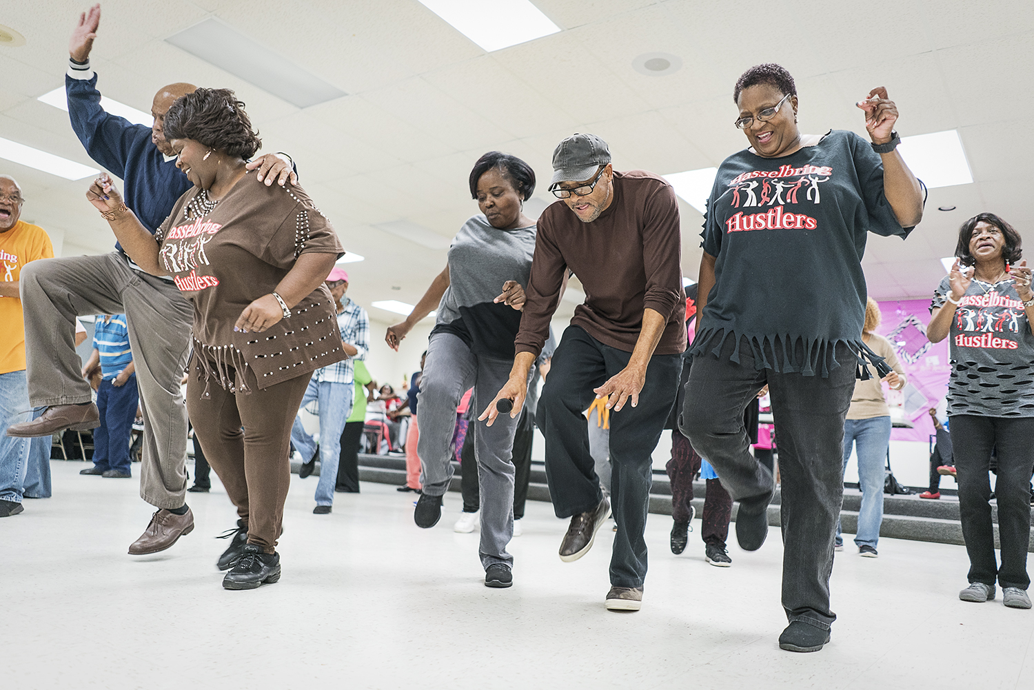"Flint, MI - Tuesday, October 24, 2017: Flint resident and DJ Gardell Haralson, 64, center right, takes a dance break from emceeing and joins the Hustlers at the Hasselbring Senior Community Center. ""It gave me the feeling I was doing something,"" he said about the progress of the Hustlers, ""they're not giving up on living.""