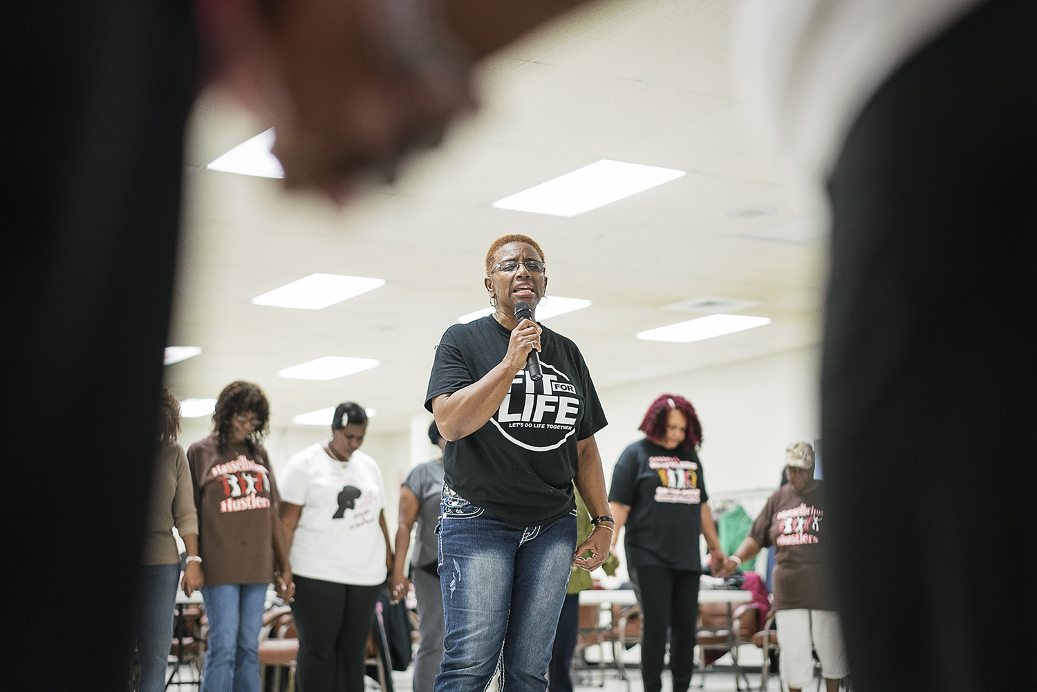 Flint, MI - Tuesday, October 24, 2017: Flint resident Queenella McGee, 66, leads the Hasselbring Hustlers in prayer before they finish their dancing for the day at the Hasselbring Senior Community Center. McGee, on her first day back from a hiatus from the Hustlers, was excited to be back dancing and active with the community.