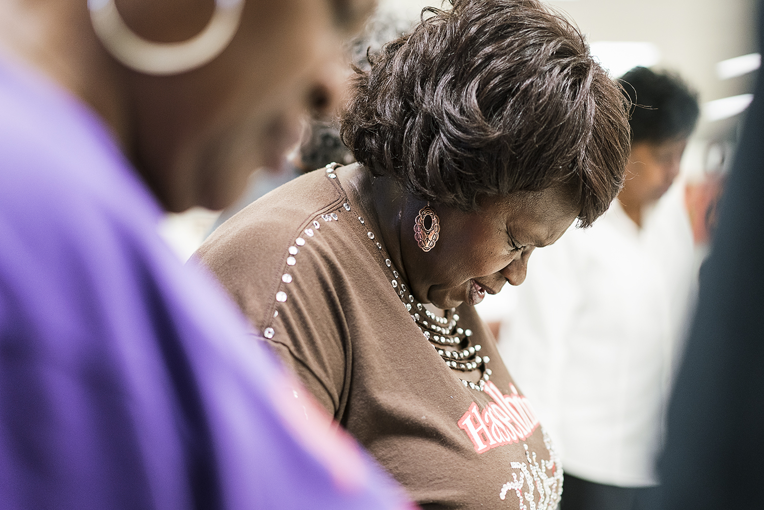 Flint, MI - Tuesday, October 24, 2017: Hasselbring Hustlers committee chairperson Marva Johnson, from Flint, bows her head during the closing prayer after nearly two hours of dancing at the Hasselbring Senior Community Center.