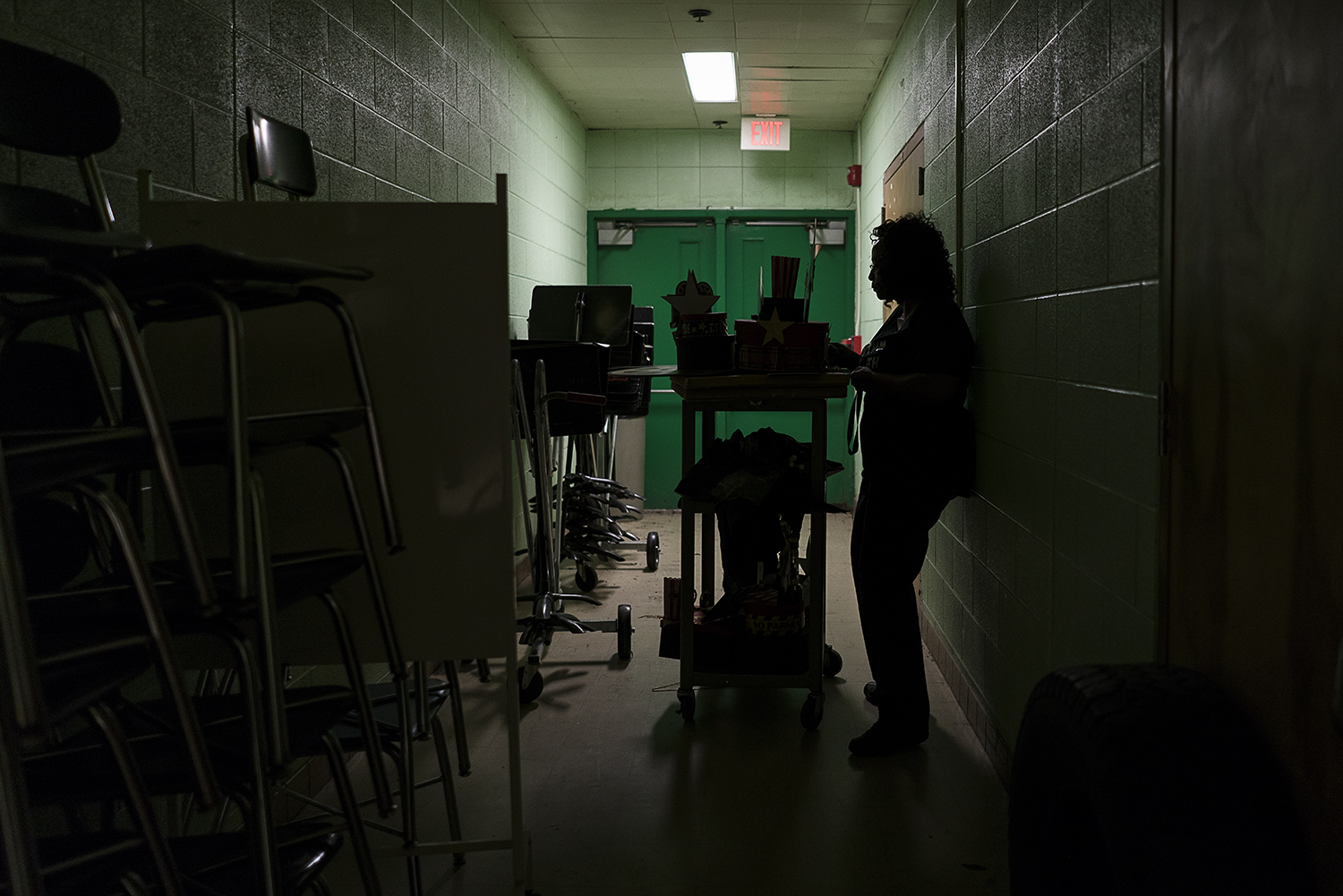 Flint, MI - Monday, October 16, 2017: In a narrow, dimly lit corridor between the band room and auditorium at Flint Northwestern High School, Flint resident Sheila Miller-Graham squeezes between her cart loaded with decorations and the wall to unlock a door to the stage. Miller-Graham has a full plate with her responsibilities as the Director of Creative Expressions Dance Studio and educator at the high school, often working more than 80 hours a week.