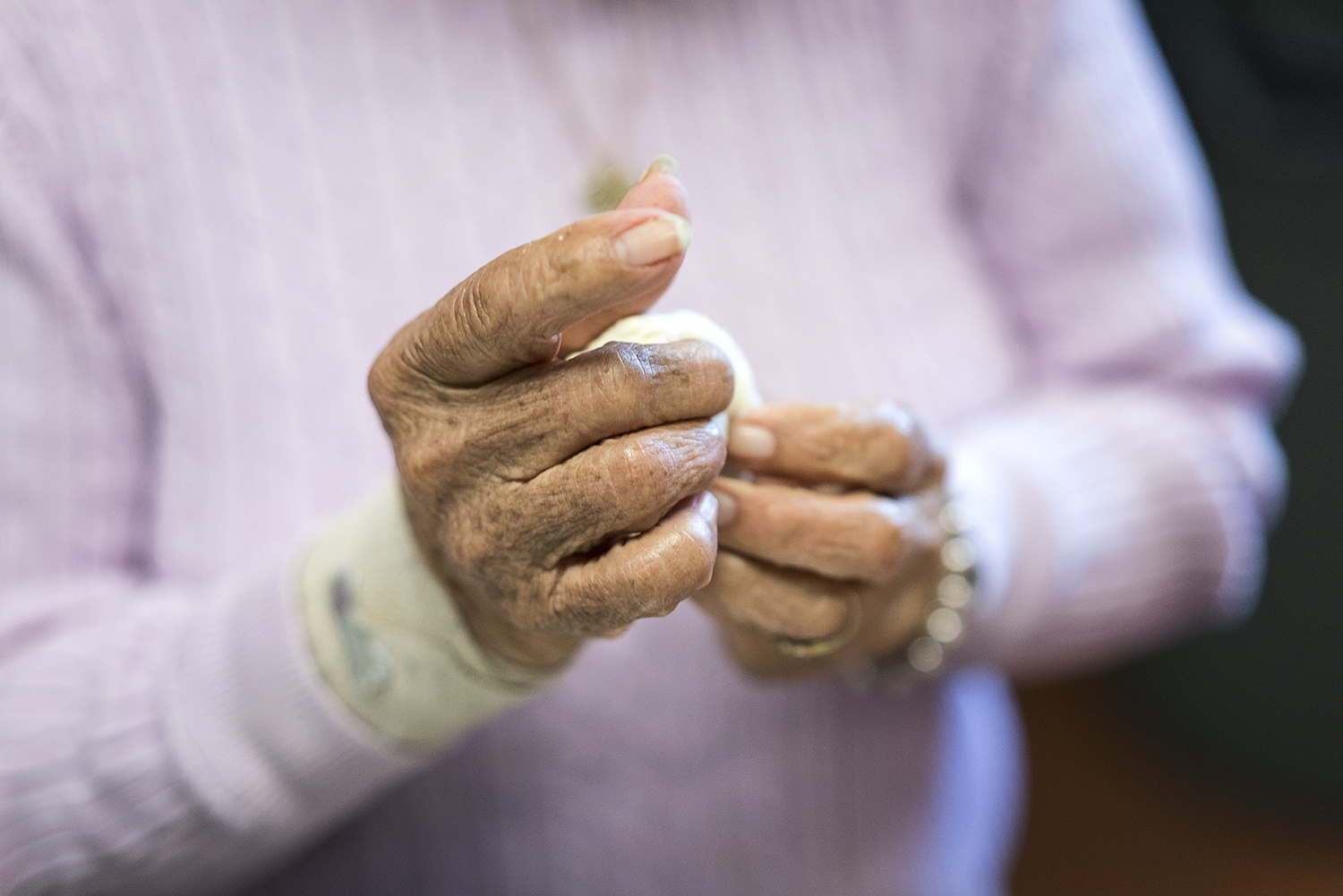 Flint, MI - Tuesday, October 17, 2017: Linda Quintanilla, 90, from Flushing, forms small balls of masa in the kitchen at the San Juan Diego Activity Center at Our Lady of Guadalupe. After the masa is tediously made into uniform balls, it is flattened into discs by hand to be cooked and packaged as tortillas. 
