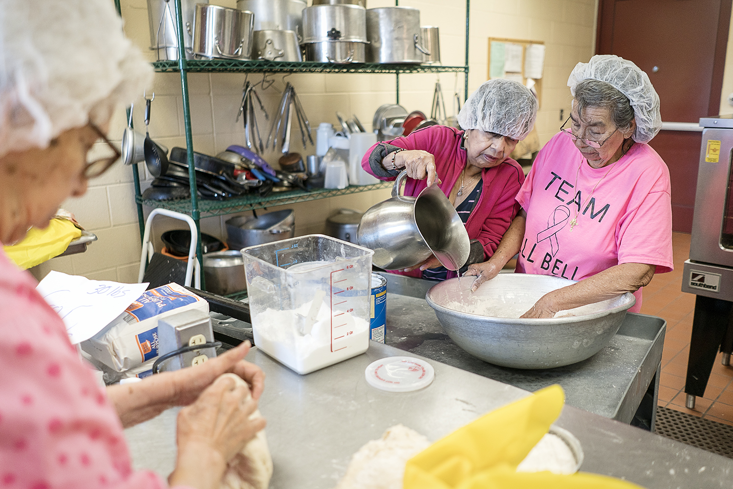 Flint, MI - Tuesday, October 17, 2017: Flint residents Connie Aguilar, left, 81, kneads a ball of masa on the countertop while Vina Shattuck, 70, center, slowly pours water into the batter for Ofelia Luna, 79, right, in the kitchen of the San Juan Diego Activity Center at Our Lady of Guadalupe. The masa will go through many hands before being packaged as stacks of tortillas.
