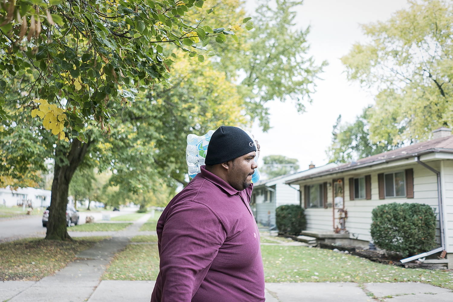 Flint, MI - Wednesday, October 25, 2017: With a case of water bouncing on his shoulder, Flint resident William Harris, 31, walks up the sidewalk to a home in the 4th Ward. Harris finds that the majority of the people receiving deliveries are grateful and he rarely experiences any type of resistance or negativity while on his route.