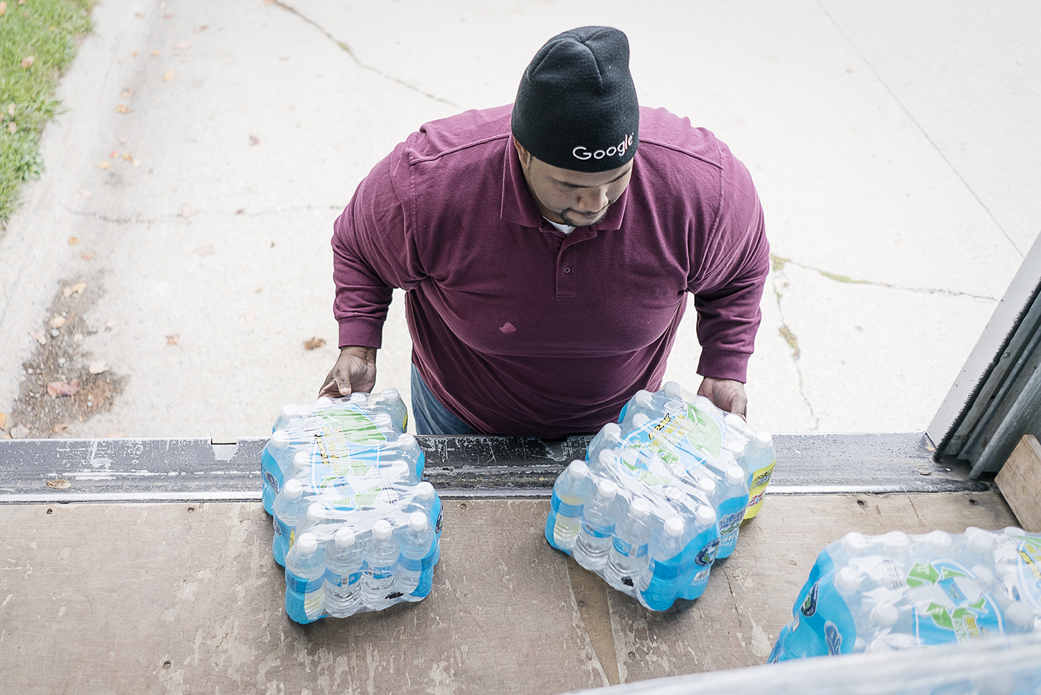 Flint, MI - Wednesday, October 25, 2017: William Harris, 31, from Flint, slides two cases of water off the back of the delivery truck he and his teammates use to provide service to residents of the 4th Ward. Harris will climb up and down repeatedly throughout the day to position water for easy delivery to the homes along the route.