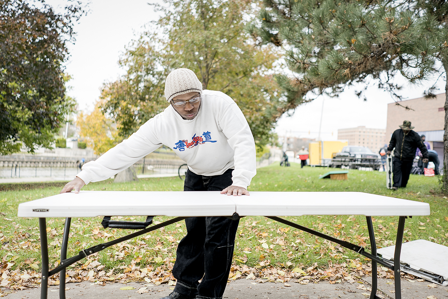 "Flint, MI - Saturday, October 28, 2017: Burton resident Paul C. Owens, 31, sets up a collapsable table at the Riverbank Park along the Flint River for the Flint Community Cookout. Owens, a self-proclaimed introvert, uses the cookout as a means to connect with others. ""I'm really shy around people, but this helps,"" he says. Owens has been volunteering for 4 years and comes ""to do the Lord's work.""