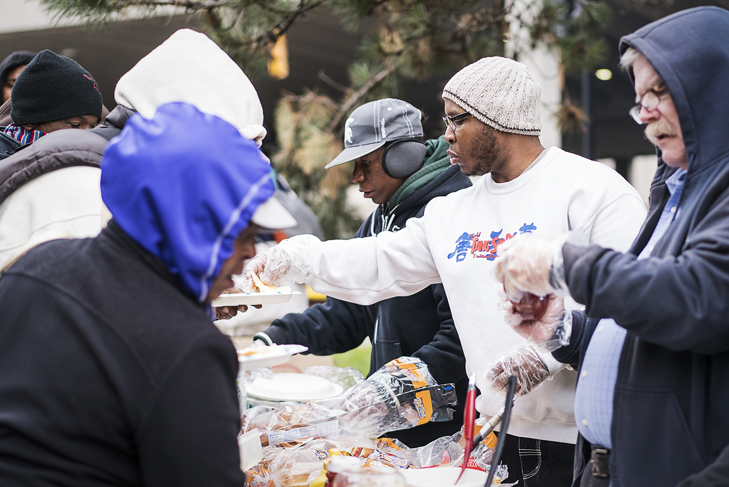 "Flint, MI - Saturday, October 28, 2017: Burton resident Paul C. Owens, 31, (center) serves up some food at the Flint Community Cookout at the Riverbank Park. Owens, a volunteer for 4 years, uses the cookouts as an opportunity to ""do the Lord's work"" and to meet people, overcoming his self-proclaimed introverted personality.