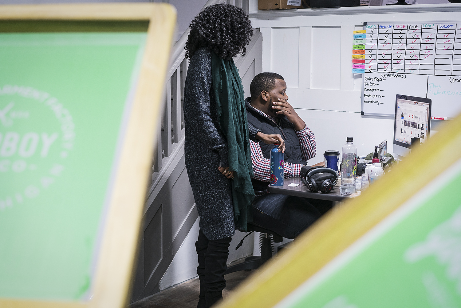 Flint, MI - Monday, November 13, 2017: GoodBoy Clothing creator and owner Oaklin Mixon, 34, of Flint, right and public relations specialist Lydia Seale, 23, of Flint look at Mixon's monitor as they plan social media and web releases of visuals in the production area of the new GoodBoy Clothing storefront.