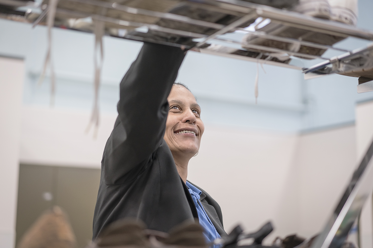 Flint, MI - Monday, December 18, 2017: Smiling as she works, Redonna Riggs, 47, of Flint, the Community Closet Coordinator at Catholic Charities Center for Hope assists clients from all backgrounds get necessities such as clothing and personal hygiene products.Tim Galloway for FlintSide