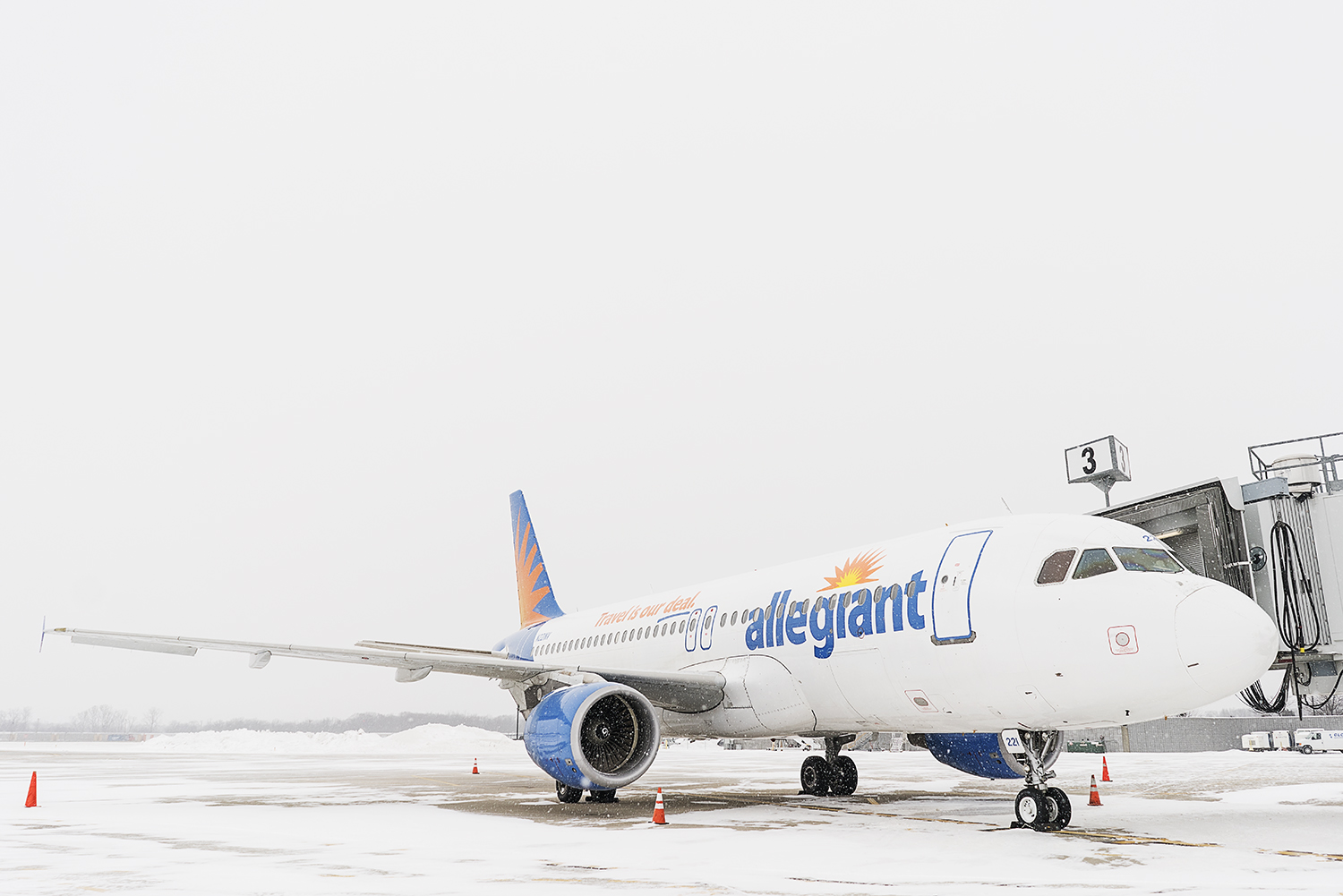 Flint, MI - Wednesday, January 3, 2018: An airplane, part of the Allegiant fleet, waits on the tarmac to be boarded and loaded with luggage at Bishop International Airport.