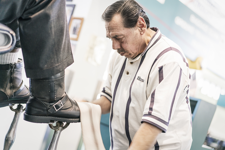 Flint, MI - Friday, January 26, 2018: Joe Garza, 69, of Mt. Morris shines a customer's shoes at the shoe shine stand at Bishop International Airport.Tim Galloway for FlintSide